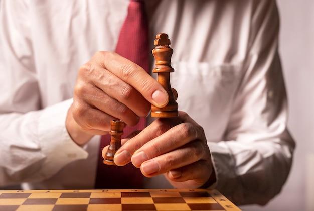 Stratégie d'entreprise et concept changeant. mains mâles enlevant le roi et la tour.