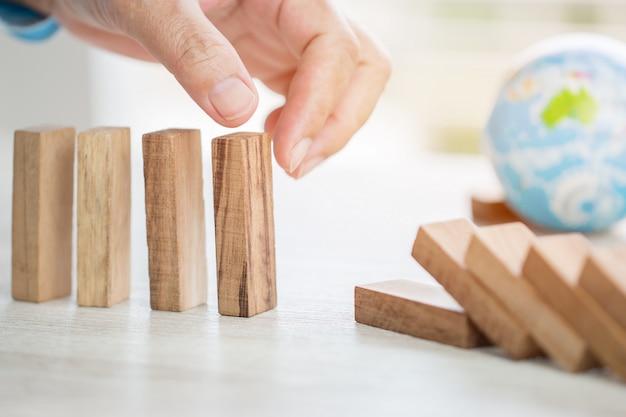 Stratégie de planification des risques dans le concept d'entreprise: homme d'affaires ou ingénieur plaçant un bloc de bois