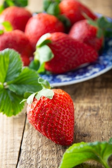 Strawberrie d'été fraîche et savoureuse. bouchent les fraises mûres sur planche de bois. lumière du jour de l'été