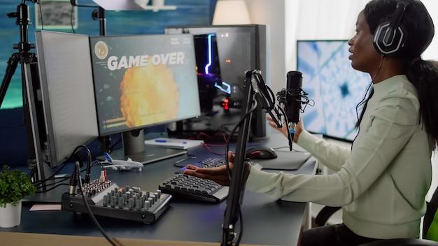 Un streamer africain professionnel perd un jeu vidéo de tir spatial lors d'une compétition en direct depuis un home studio