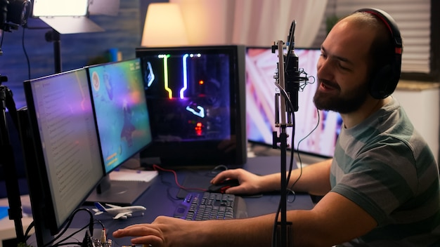 Streamer cyber exécutant un jeu vidéo de tir spatial sur un ordinateur puissant parlant avec des joueurs sur un chat ouvert pendant une compétition professionnelle