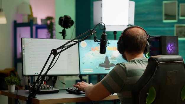 Un streamer professionnel a remporté le jeu vidéo de tir spatial lors d'une compétition en direct depuis un home studio. cyber-streaming en ligne lors d'un tournoi de jeu à l'aide d'un ordinateur puissant avec des lumières rvb