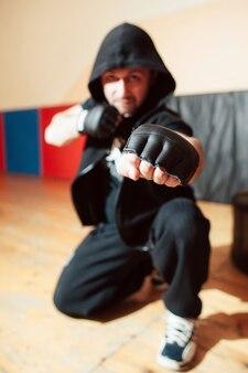 Street fighter masculin en vêtements de sport noir prêt à se battre