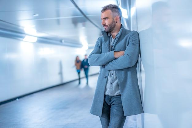 Street style, jeune brune de race blanche dans le métro avec une veste américaine grise