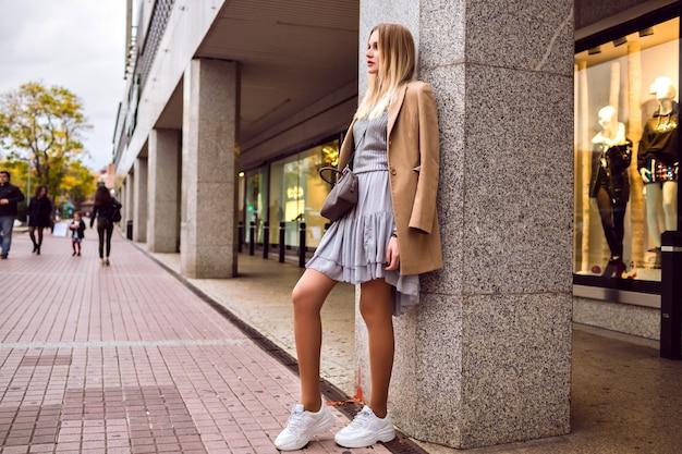 Street style mode portrait d'une femme blonde glamour élégante posant sur la rue européenne près du centre commercial, pull élégant et manteau en cachemire, couleurs toniques, printemps.