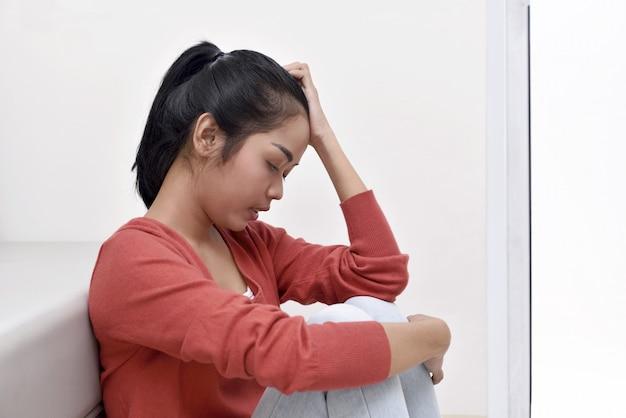 Stress asiatique femme étreignant son genou