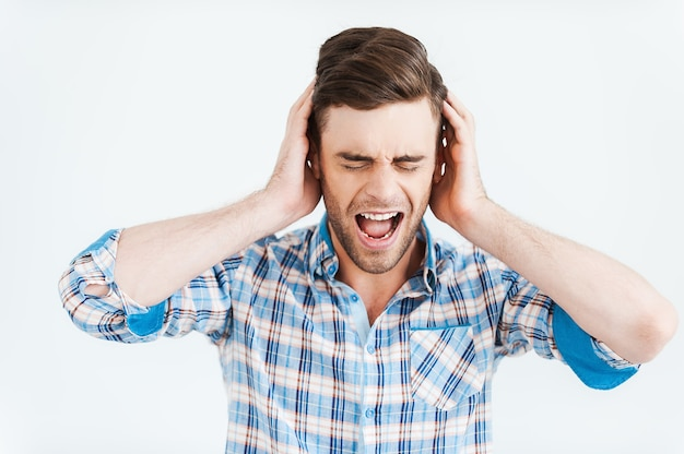 Stress émotionnel. jeune homme frustré tenant les mains sur les oreilles et gardant les yeux fermés