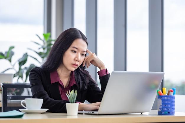 Le stress d'une jeune femme d'affaires asiatique réfléchie et bouleversée sur le lieu de travail travaillant avec un ordinateur portable du personnel de bureau n'est pas satisfait des collègues de travail derrière le bureau