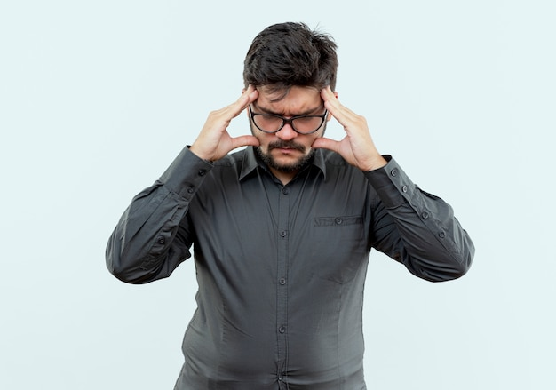 Stress jeune homme d'affaires portant des lunettes mettant la main sur le front isolé sur blanc