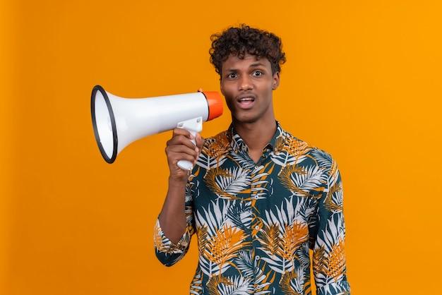 Stressant et confus jeune bel homme à la peau sombre avec des cheveux bouclés en chemise imprimée de feuilles tenant un mégaphone sur fond orange