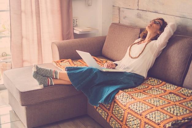 Stressé belle femme d'âge moyen travaillant sur un ordinateur portable sur le canapé à la maison. bureau alternatif internet pour travailleur numérique en ligne. fatigué de regarder en haut, portant des chaussettes amusantes