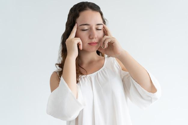 Stressé belle femme touchant les temples et réfléchissant