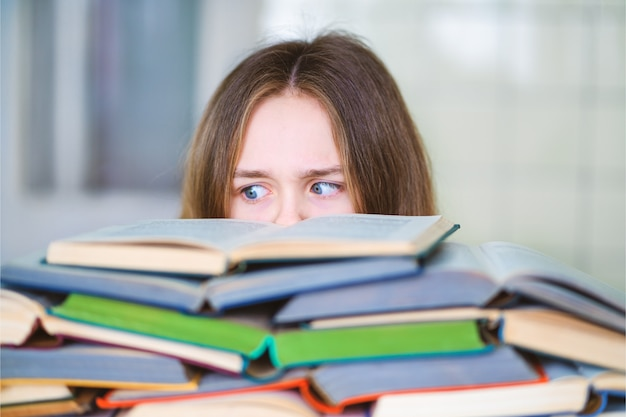 Stressé étudiant collégial fatigué d'apprendre dur avec des livres dans la préparation aux tests d'examens, submergée adolescente de lycée épuisée par des études difficiles ou trop de devoirs, concept cram