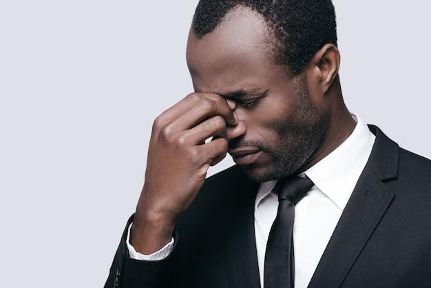 Stressé et fatigué. jeune homme africain en tenue de soirée massant le nez et gardant les yeux fermés en se tenant debout sur fond gris