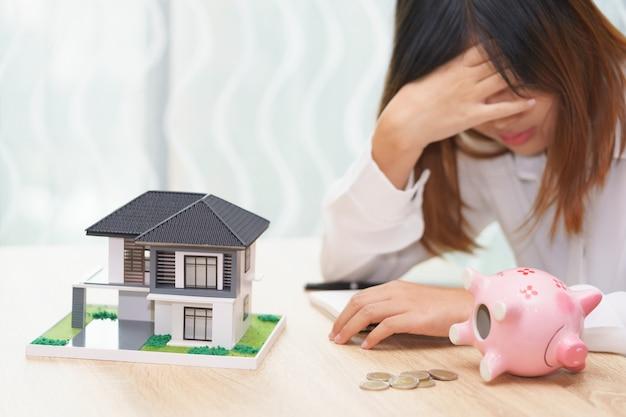 Stressé femme à court d'argent en tirelire et sa maison