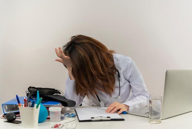 Stressé femme médecin d'âge moyen portant une robe médicale et un stéthoscope assis au bureau avec presse-papiers d'outils médicaux et ordinateur portable mettant les mains sur la tête et sur le bureau isolé