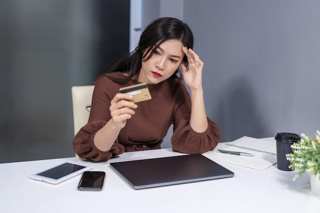 Stressé femme tenant une carte de crédit avec un ordinateur portable sur une table
