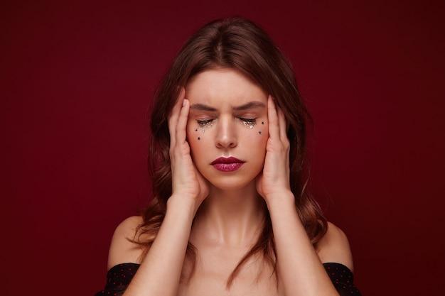 Stressé jeune femme brune avec des boucles à la recherche de fatigue et tenant son visage avec les mains, gardant les yeux fermés et fronçant les sourcils tout en posant sur fond bordeaux