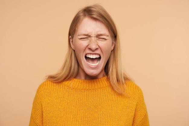 Stressé jeune femme rousse aux cheveux longs avec une coiffure décontractée en gardant les yeux fermés tout en grimaçant de travers son visage, isolé sur beige