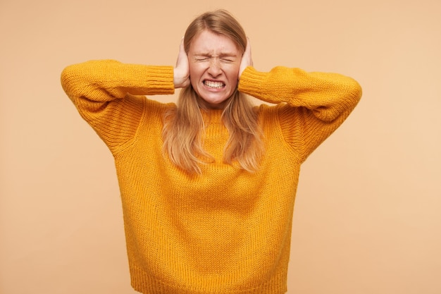 Stressé jeune femme rousse fronçant les sourcils avec les yeux fermés et fermant les oreilles avec les mains levées tout en évitant les sons forts, debout sur beige