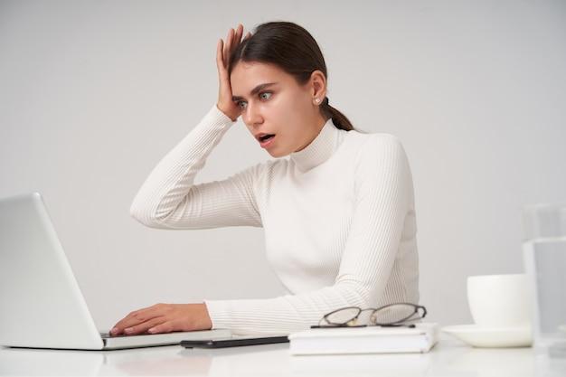 Stressé jeune jolie femme aux cheveux noirs en poloneck tricoté blanc travaillant avec son ordinateur portable sur un mur blanc, lisant des nouvelles inattendues avec un visage choqué