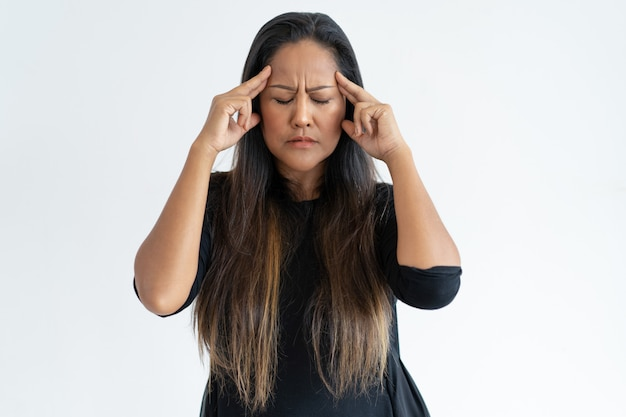 Stressée femme d'âge moyen touchant les temples et réfléchissant