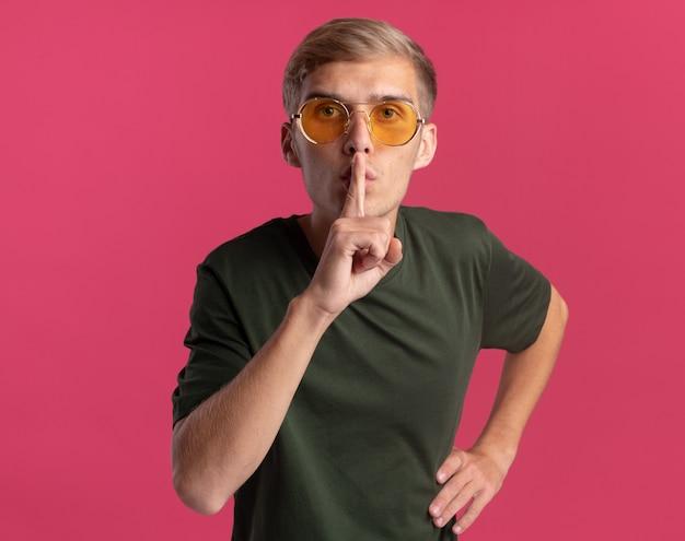 Strict jeune beau mec portant une chemise verte et des lunettes montrant un geste de silence mettant la main sur la hanche isolé sur un mur rose