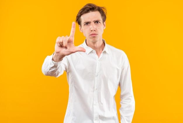 Strict jeune beau mec vêtu d'une chemise blanche montrant un geste de perdant isolé sur un mur orange