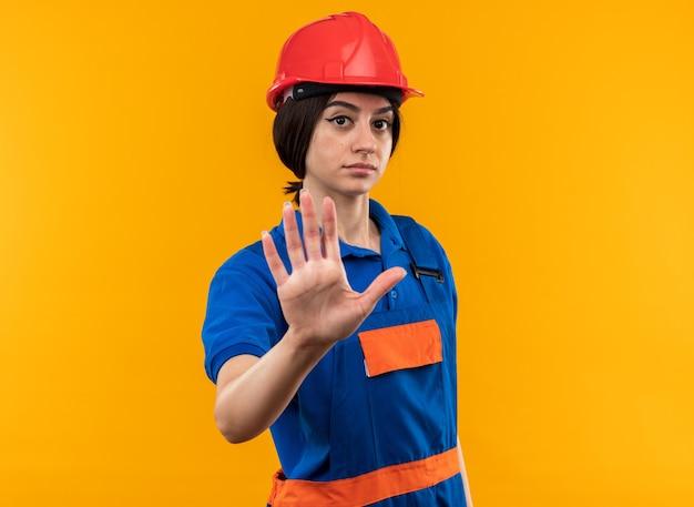 Strict looking at camera jeune constructeur femme en uniforme montrant un geste d'arrêt
