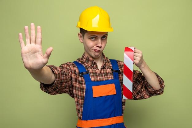 Strict montrant le geste d'arrêt jeune constructeur masculin portant l'uniforme tenant du ruban adhésif