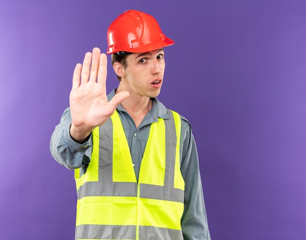 Strict regardant la caméra jeune homme constructeur en uniforme montrant le geste d'arrêt