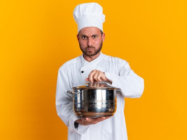 Strict young caucasian male cook en uniforme de chef et cap holding pot saisissant le couvercle du pot