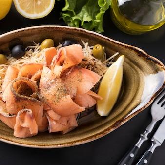 Stroganina de saumon cru surgelé en tranches sur une assiette de fromage, d'olives et de citron. stroganina - poisson surgelé tranché