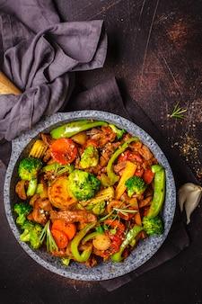 Stroganoff de bœuf frit avec pommes de terre et légumes dans une casserole, vue de dessus.