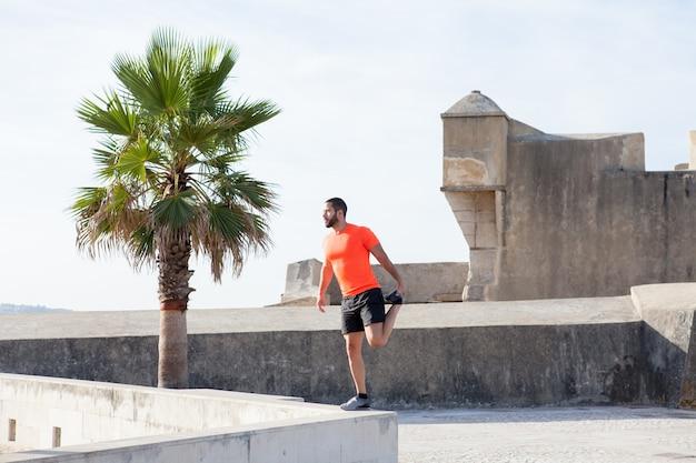 Strong sportsman stretching leg on parapet