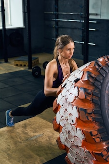 Strong woman flipping tire dans crossfit