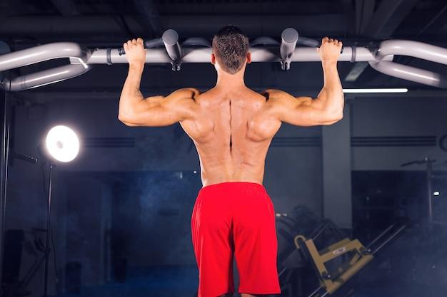 Strong young man doing pull up exercice sur barre horizontale dans la salle de sport