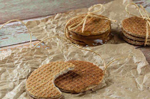 Stroopwafel avec une bouchée sur du papier brun à côté d'un autre biscuit et ficelle de sisal (vue latérale).