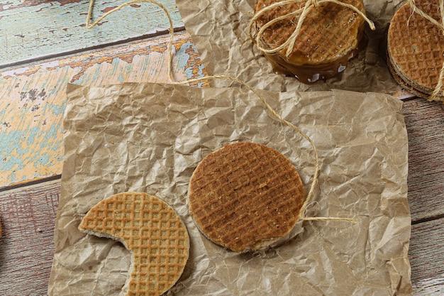 Stroopwafel avec une bouchée sur du papier brun à côté d'un autre biscuit et ficelle de sisal.