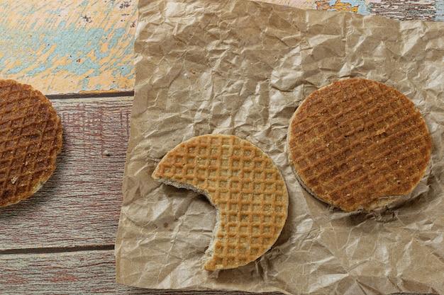 Stroopwafel avec une bouchée sur du papier brun à côté d'un autre cookie (vue de dessus).