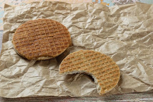 Stroopwafel avec une bouchée sur du papier brun à côté d'un autre cookie.