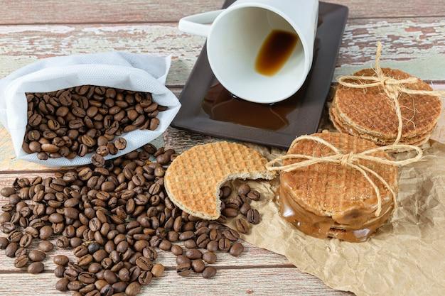 Stroopwafels avec une bouchée sur des grains de café et à côté d'une tasse.