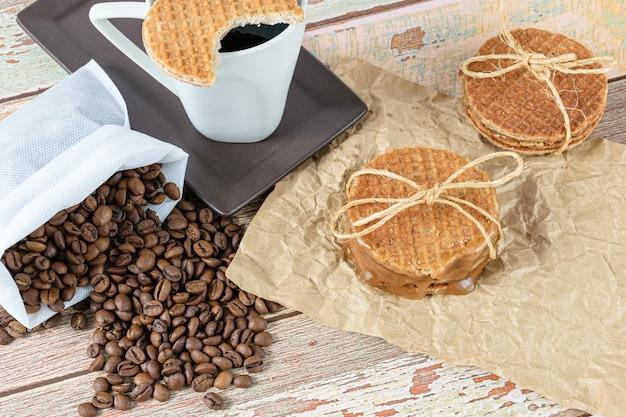 Stroopwafels empilés sur du papier brun, à côté de haricots et d'une tasse de café.