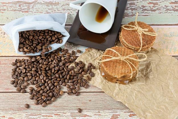 Stroopwafels empilés sur du papier brun, à côté d'une tasse à café allongée (vue de dessus).
