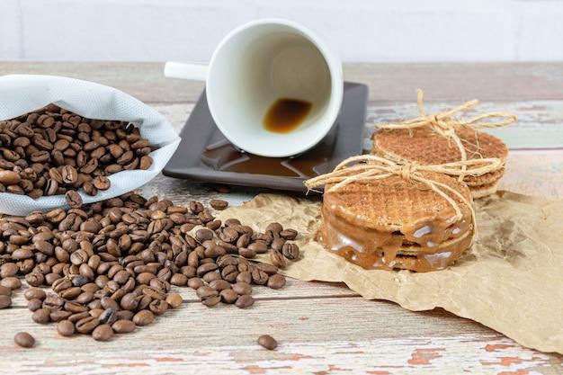 Stroopwafels empilés sur du papier brun, à côté d'une tasse à café allongée.