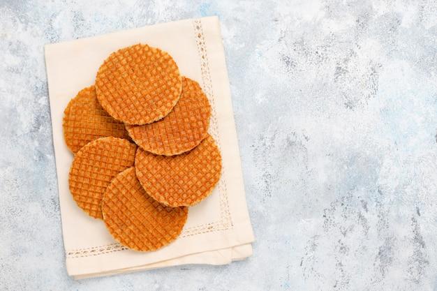 Stroopwafels, gaufres hollandaises au caramel avec thé ou café et miel sur béton