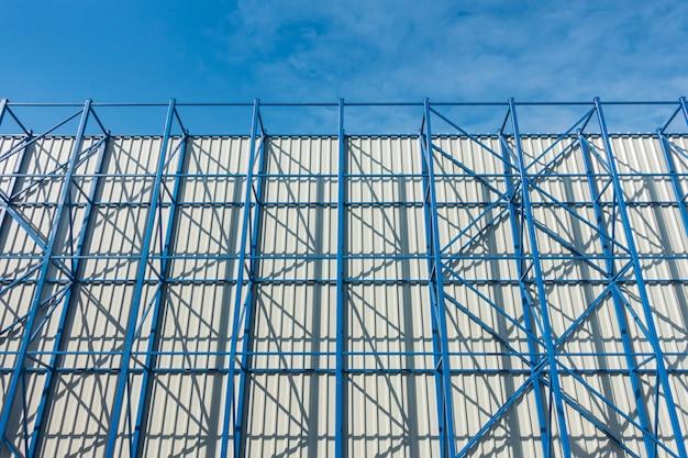Structure en acier et revêtement mural en tôle avec ciel bleu.