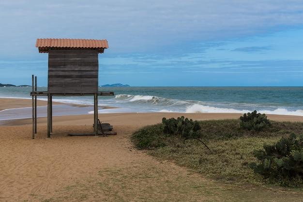 Structure en bois en forme de maison de sauveteur sur la plage de rio das ostras à rio de janeiro. journée partiellement nuageuse, ciel bleu et quelques nuages. mer forte et sable jaunâtre et beaucoup de rochers.