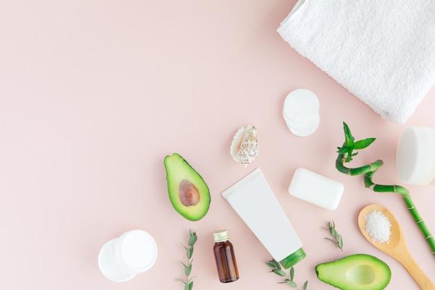 Structure de cadre de spa et de bien-être rose-vert avec serviette, bambou, feuilles tropicales, avocat, bouteille d'huile, outils de soin du corps et du visage au pastel.