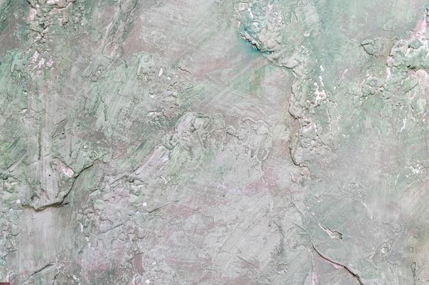 Structure d'une dalle poreuse non uniforme située à côté. ciment, texture rustique et concrète, fond non uniforme. vert en relief, surface grise